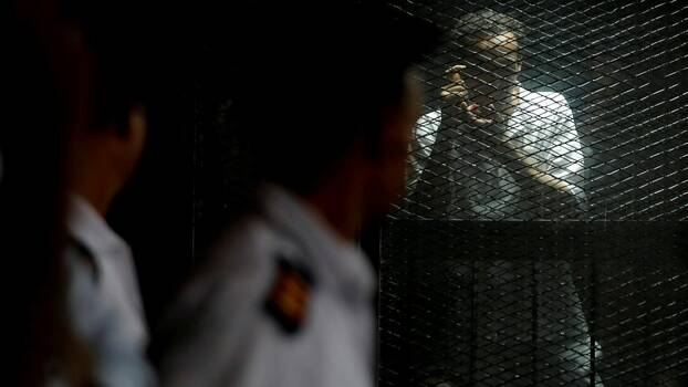Egyptian photojournalist Mahmoud Abu Zeid, also know as Shawkan, reacts behind a fence during his trial in Cairo, Egypt July 28, 2018